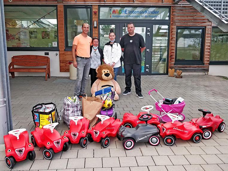 Das Bild zeigt die Spender Attila, Gülcan, Leonie und David hinter Taschen mit Spielsachen und Bobby Cars